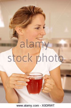 WOMAN IN KITCHEN DRINKING FRUIT TEA - Stock Photo