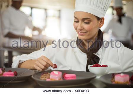 Smiling female chef finishing dessert plates - Stock Photo