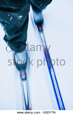 Low section of a person cross-country skiing - Stock Photo