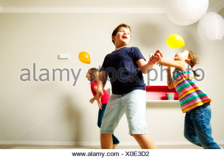 Children in living room playing with balloons, Munich, Bavaria, Germany - Stock Photo