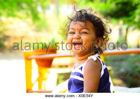 Cute baby laughing facing camera - Stock Photo