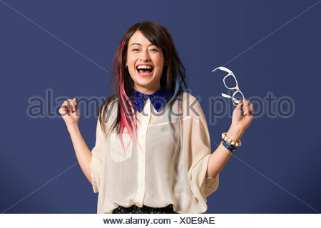 Portrait of young woman with dyed hair holding glasses - Stock Photo