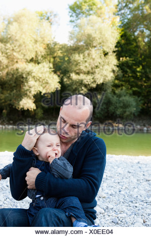 Father holding crying baby by creek - Stock Photo