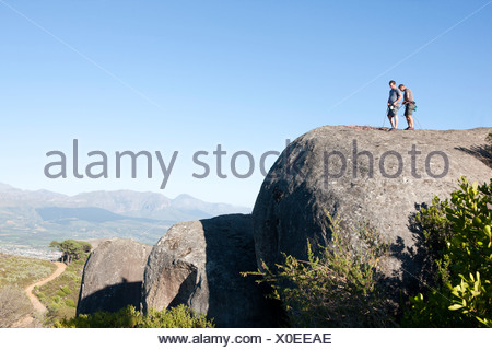 Young male climbers attaching ropes and harnesses on rock - Stock Photo