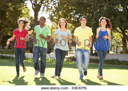 Group Of Teenagers Running Through Park - Stock Photo