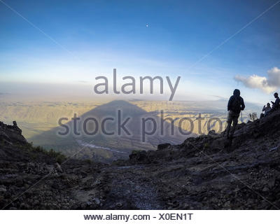 People watching the shadow of Ol Doinyo Lengei (The Mountain of God) stretch across Lake Natron below at dusk, Rift Valley, Tanzania 2015 - Stock Photo