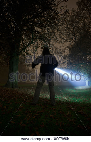 Germany, Munich, Young man with torch in foggy night - Stock Photo