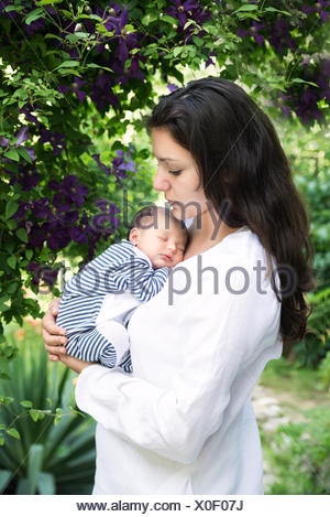 Mother holding sleeping baby in garden - Stock Photo