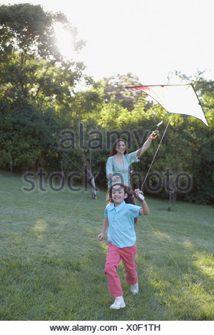 Young girl and woman outdoors flying kite and smiling - Stock Photo