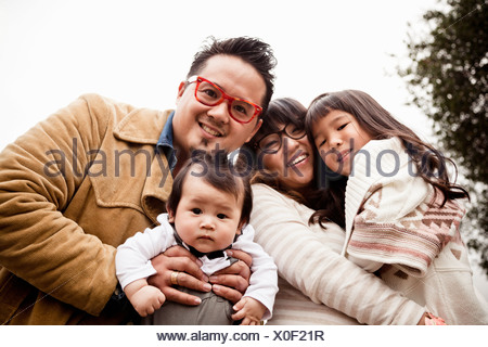 Family portrait of mid adult couple with daughter and baby boy in park - Stock Photo