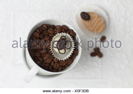 Cup of coffee with coffee beans and petit four, elevated view - Stock Photo