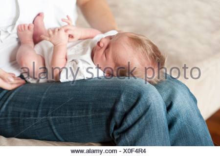 Mother holding infant son on lap - Stock Photo