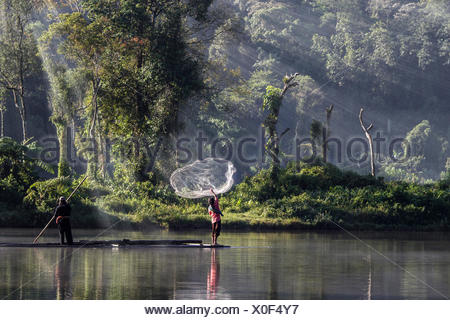 Indonesia, West Java, Karawang, Situ Gunung, Man throwing fishing net into water - Stock Photo
