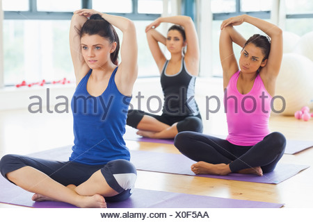 Class stretching hands behind heads on mats at yoga class - Stock Photo
