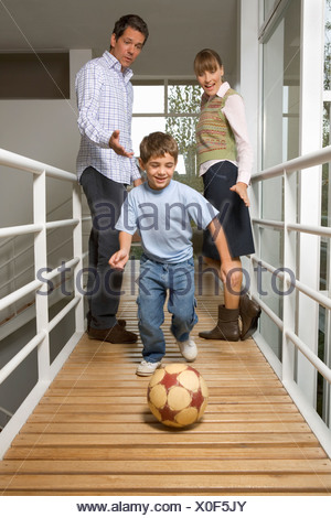 Young boy playing soccer in the house - Stock Photo