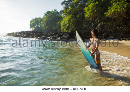Mid adult woman on the beach standing in the surf holding her board, Bali, Indonesia - Stock Photo