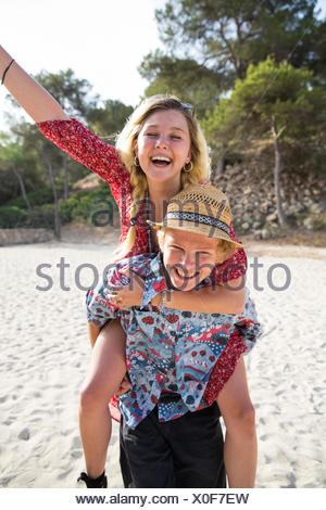 Man on beach giving smiling woman piggyback, Majorca, Spain - Stock Photo