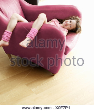 young girl relaxing upside-down in chair - Stock Photo