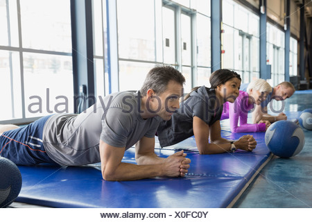 Group doing planks in exercise class at gym - Stock Photo