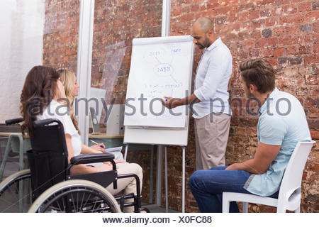 Businessman making a presentation to his fellow coworkers - Stock Photo