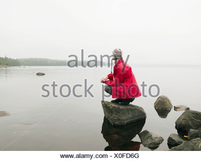 Woman crouching on large rock in the water. - Stock Photo