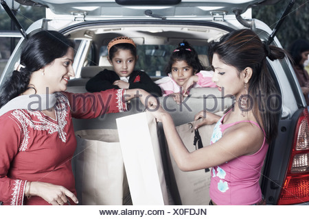 Portrait of two girls leaning against a car seat with their sister and their mother in the back - Stock Photo