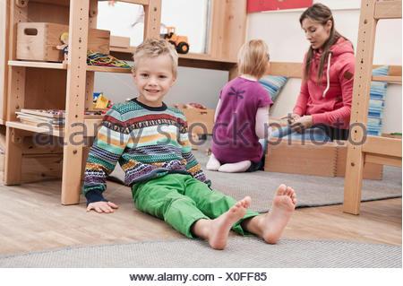 Little boy sitting on the ground in his kindergarten - Stock Photo