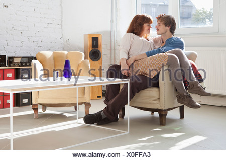 A young woman sitting comfortably in her boyfriend's lap