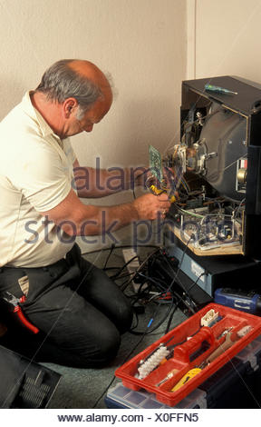 man repairing or taking an old analogue television to pieces - Stock Photo