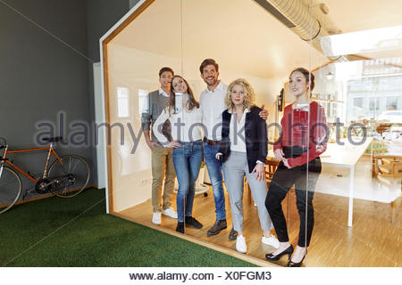 Business team standing in modern office - Stock Photo