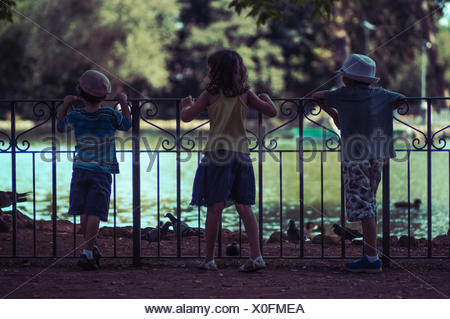 Three children looking at ducks on a lake, Italy - Stock Photo