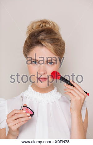 Portrait of a woman using make-up brush on face - Stock Photo