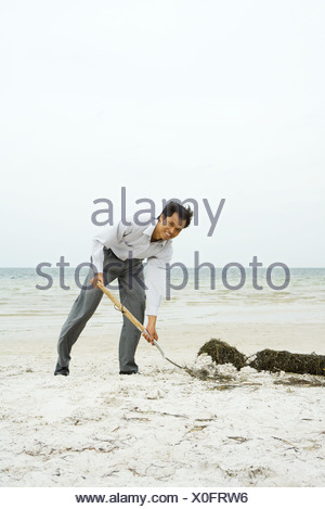 Man at the beach scooping sand with shovel, smiling at camera, full length - Stock Photo