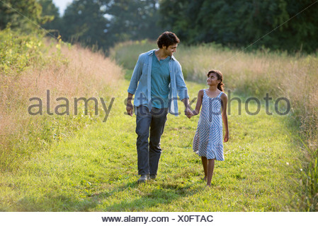 A man and a young girl walking down a mown path in the long grass holding hands. - Stock Photo