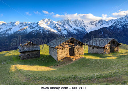 Meadows and alpine huts framed by snowy peaks at dawn Tombal Soglio Bregaglia Valley canton of Graubünden Switzerland Europe - Stock Photo