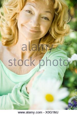 Senior woman holding out flower, portrait - Stock Photo