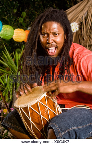 Young Jamaican man with dreadlocks playing bongo on tropical island - Stock Photo
