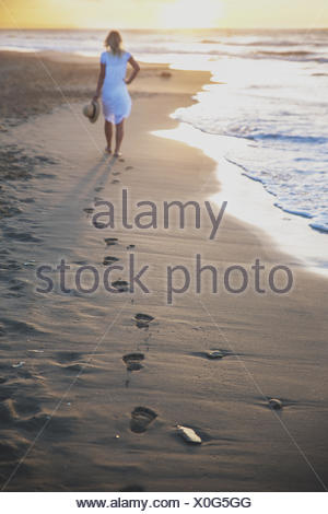 Beautiful woman walking on the beach with her footprints back - Stock Photo