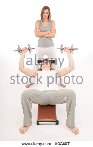 Fitness - young man exercising on bench with weights - Stock Photo