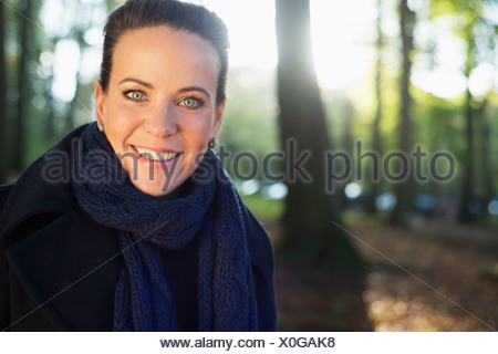 Portrait of mid adult woman in woodland park - Stock Photo