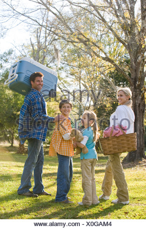 Family going on picnic in park - Stock Photo