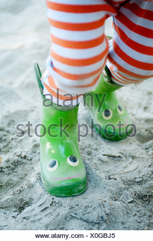 Legs of young male toddler wearing smiley wellington boots - Stock Photo