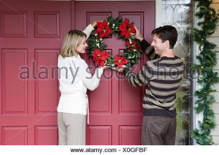 Couple hanging Christmas wreath - Stock Photo