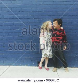 Portrait of a Boy and girl with their arms around each other - Stock Photo