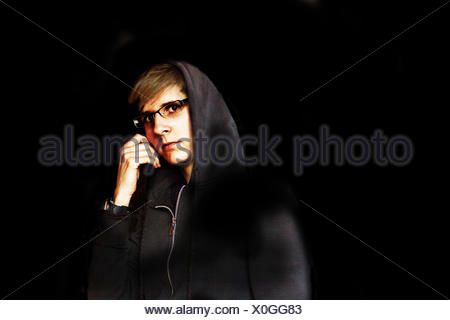 Young woman in sweat jacket with hood in the dark - Stock Photo