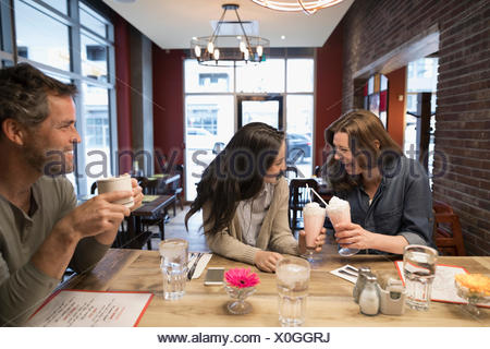 Mother and teenage daughter toasting milkshakes at diner counter - Stock Photo