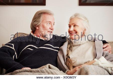 Senior couple sitting on sofa, smiling
