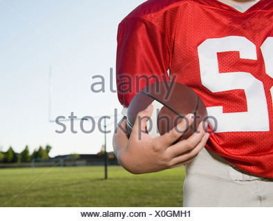 Close up of football player holding football on field - Stock Photo