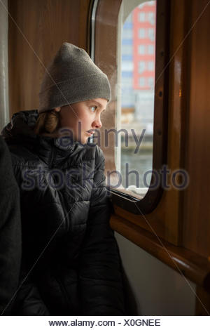 Boy looking out of a boat window - Stock Photo