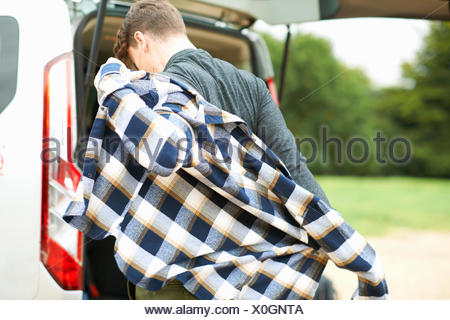 Rear view of man by automobile boot putting on plaid shirt - Stock Photo